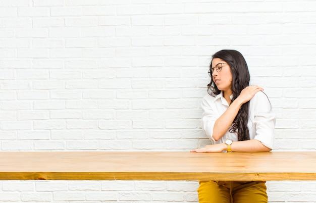Giovane bella donna latina sentirsi stanca, stressata, ansiosa, frustrata e depressa, con dolore alla schiena o al collo seduto davanti a un tavolo