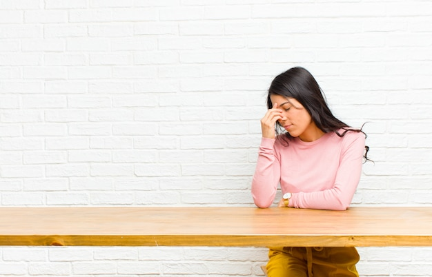 Giovane bella donna latina sentirsi stressata, infelice e frustrata, toccando la fronte e soffrendo di emicrania di forte mal di testa seduto davanti a un tavolo