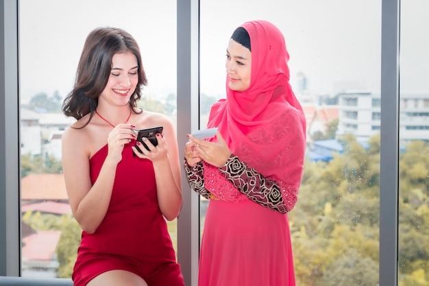 Giovane bella donna musulmana e amicizie caucasiche con telefono e carta di credito godendo nello shopping