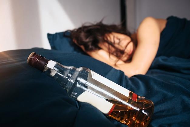 Giovane bella donna nel letto di mattina a casa. dormire dopo una festa di alcolici. bottiglia di whisky sul letto inoltre. il sole splende nella stanza.