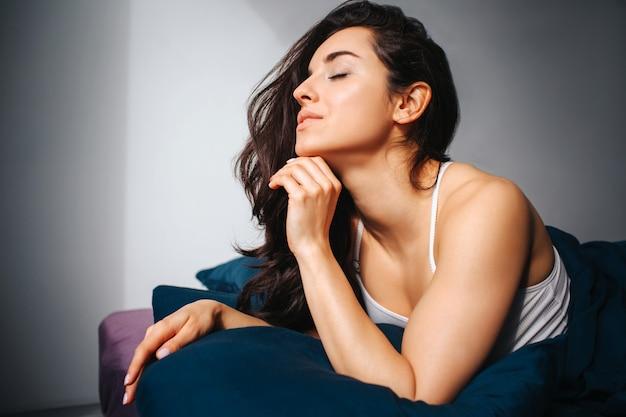 Giovane bella donna nel letto di mattina a casa. posign di modello femminile attraente sexy vago con gioia. sdraiato sul letto con gli occhi chiusi e tieni una mano sotto il mento.