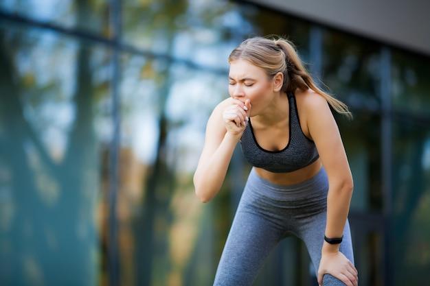 Giovane bella donna nel parco che indossa abbigliamento sportivo