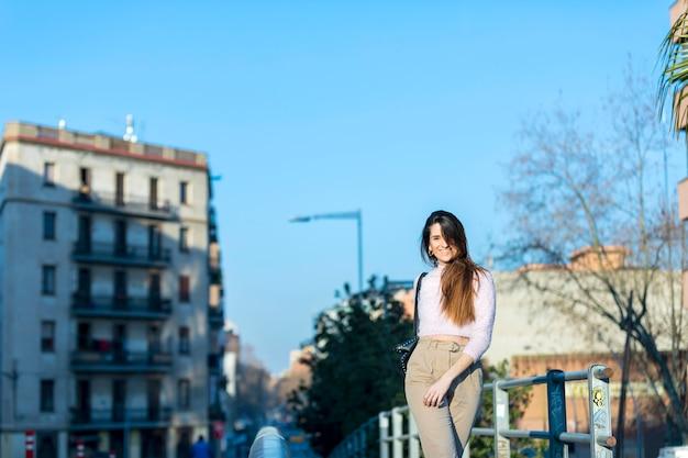 Giovane bella donna nell'abbigliamento casual che cammina all'aperto nella città