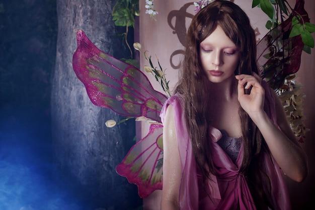 Giovane bella donna nell'immagine delle fate, foresta oscura magica