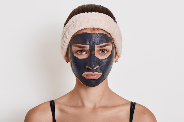 Giovane bella donna nella maschera nera del fango