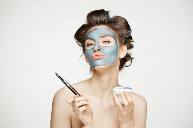 Giovane bella donna nuda in bigodini che copre il viso di mack. trattamento facciale. cosmetologia e spa di bellezza.