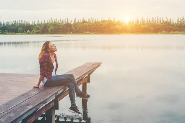 Giovane bella donna pantaloni a vita bassa seduta sul molo del lago, rilassato