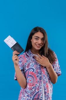 Giovane bella donna piacevole del viaggiatore con i biglietti e il passaporto che tengono la mano sul petto riconoscente, sorridente amichevole sopra la parete blu
