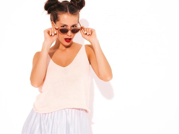Giovane bella donna ragazza d'avanguardia nella rappresentazione casuale dei vestiti di estate. la femmina positiva mostra le emozioni facciali. modello divertente isolato su bianco