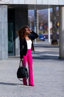 Giovane bella donna riccia che indossa abiti eleganti e borsetta mentre si trovava in strada in una giornata di sole