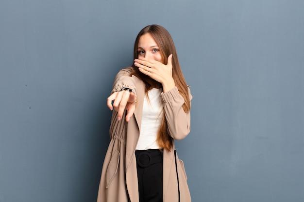 Giovane bella donna ridendo di te, indicando e prendendo in giro o prendendo in giro contro il muro grigio