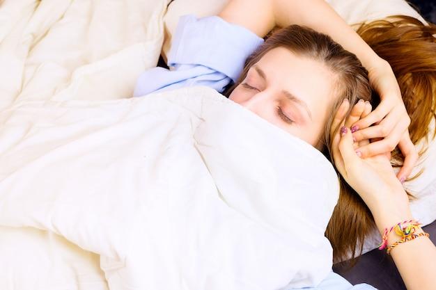 Giovane bella donna sdraiata nel suo letto, viso coperto da una coperta con gli occhi chiusi. , concetto di sonno di mattina o di notte.