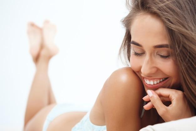 Giovane bella donna sdraiata sul letto nelle prime ore del mattino