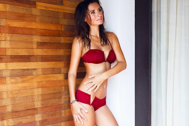 Giovane bella donna seducente con un corpo perfetto, posa in bikini sexy in villa di lusso, rilassata durante le sue vacanze, ha i capelli bagnati e trucco luminoso.