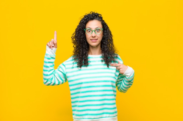 Giovane bella donna sentendosi orgogliosa e sorpresa, indicando con fiducia se stessa, sentendosi come il numero uno di successo contro la parete arancione