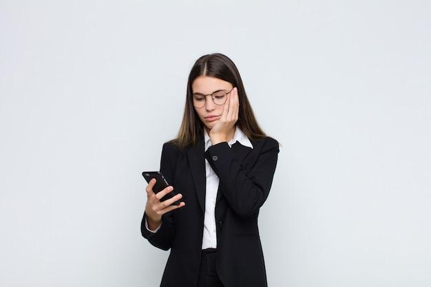 Giovane bella donna sentirsi annoiata, frustrata e assonnata dopo un compito noioso, noioso e noioso, tenendo il viso con la mano con un telefono cellulare