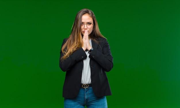 Giovane bella donna sentirsi preoccupata, fiduciosa e religiosa, pregando fedelmente con i palmi premuti, chiedendo perdono contro la parete verde