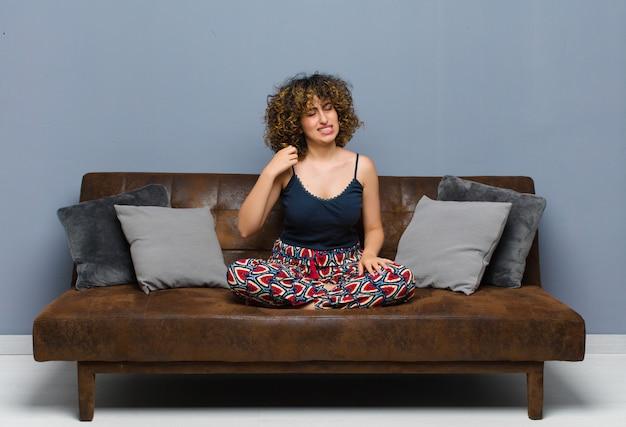 Giovane bella donna sentirsi stressata, ansiosa, stanca e frustrata, tirando il collo della camicia, guardando frustrata dal problema seduto su un divano.