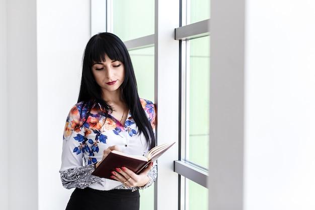 Giovane bella donna seria in piedi vicino alla finestra, scrivendo nel taccuino, guardando al notebook.