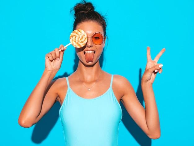 Giovane bella donna sexy hipster con labbra rosse in occhiali da sole. ragazza di tendenza in costumi da bagno estate. femmina positiva che impazzisce. modello divertente isolato sull'azzurro. mangiare la lecca-lecca della caramella