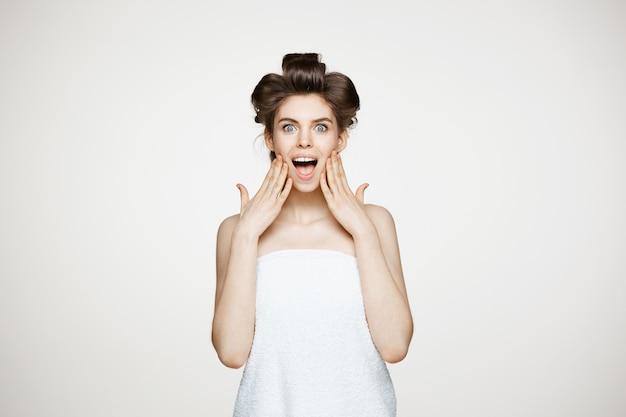 Giovane bella donna sorpresa in bigodini che sorride con la bocca aperta. concetto di bellezza e spa.
