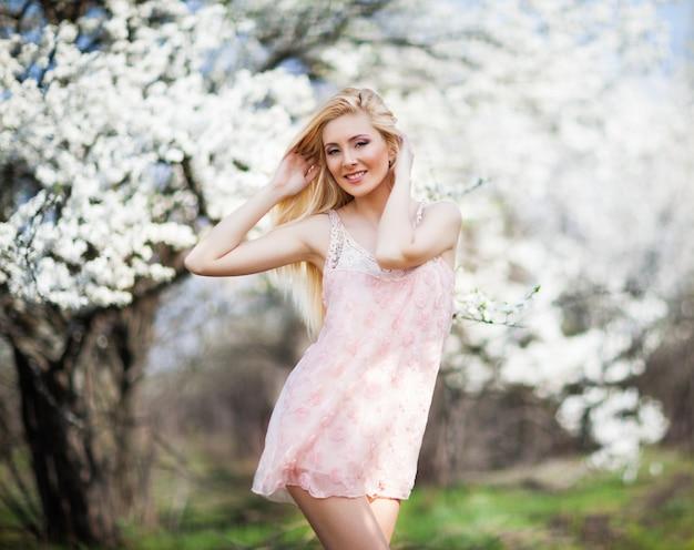 Giovane bella donna sorridente bionda in mini abito bianco in piedi con alberi in fiore sullo sfondo