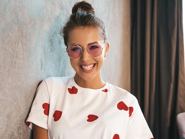 Giovane bella donna sorridente che guarda l'obbiettivo ragazza d'avanguardia in abito bianco estivo casual e occhiali da sole
