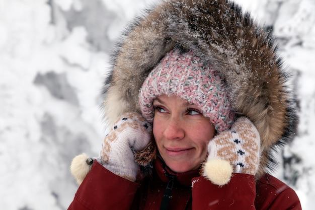 Giovane bella donna sorridente che guarda lateralmente in cappello tricottato rosa con pompon in rivestimento caldo all'aperto