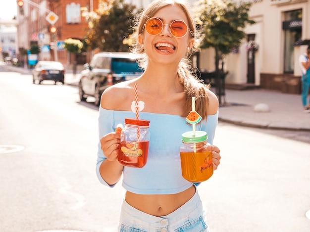Giovane bella donna sorridente dei pantaloni a vita bassa in occhiali da sole.