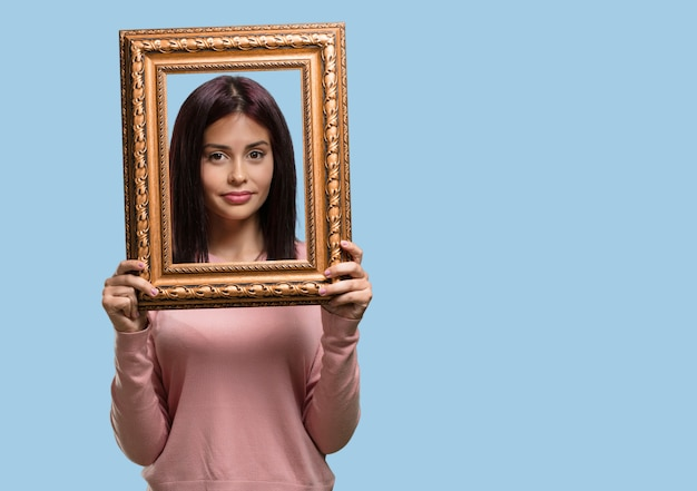Giovane bella donna sorridente e rilassata, guardando attraverso una cornice, foto divertente e creativo