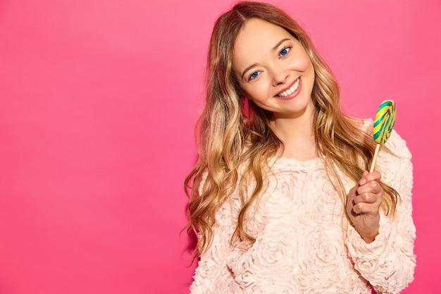 Giovane bella donna sorridente hipster in abiti estivi alla moda. donna spensierata sexy che posa vicino alla parete rosa. lecca-lecca mangiante di modello positiva