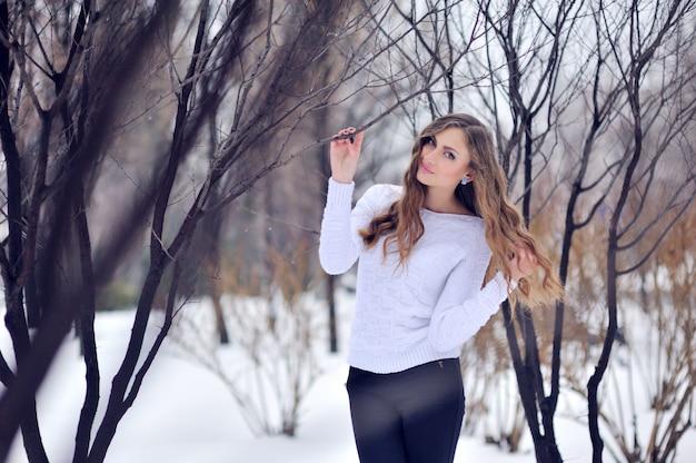 Giovane bella donna sorridente nella foresta di inverno