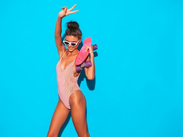 Giovane bella donna sorridente sexy dei pantaloni a vita bassa in occhiali da sole ragazza alla moda in costume da bagno dello swimwear di estate. femmina positiva che impazzisce con il pattino rosa del penny, isolato sul blu.