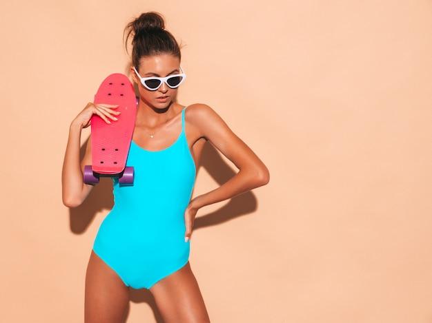Giovane bella donna sorridente sexy dei pantaloni a vita bassa in occhiali da sole ragazza alla moda in costume da bagno dello swimwear di estate. femmina positiva che impazzisce con il pattino rosa del penny, isolato sulla parete beige