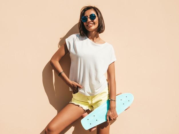 Giovane bella donna sorridente sexy dei pantaloni a vita bassa in occhiali da sole ragazza alla moda in maglietta e shorts di estate. femmina positiva con il pattino blu del penny che posa nella via vicino alla parete