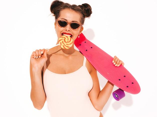 Giovane bella donna sorridente sexy hipster con labbra rosse in occhiali da sole. ragazza in costume da bagno estate costumi da bagno.
