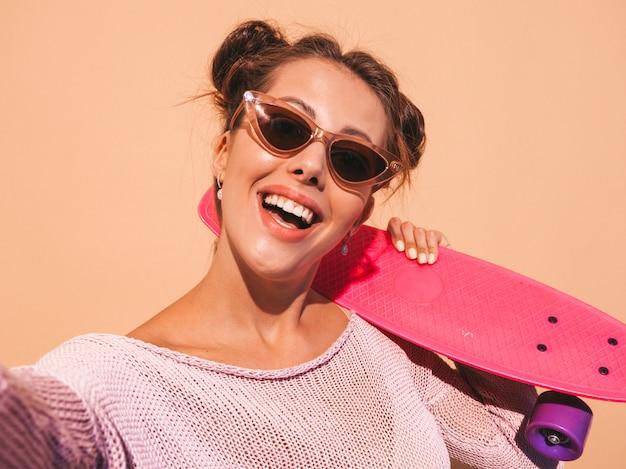 Giovane bella donna sorridente sexy hipster in occhiali da sole. ragazza di tendenza in cardigan lavorato a maglia estiva. femmina con skateboard penny rosa, isolato sulla parete beige. scattare foto di autoritratto selfie su phon