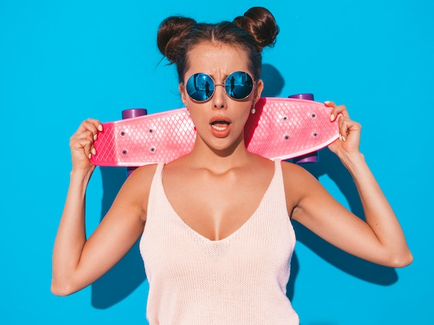 Giovane bella donna sorridente sexy hipster in occhiali da sole.