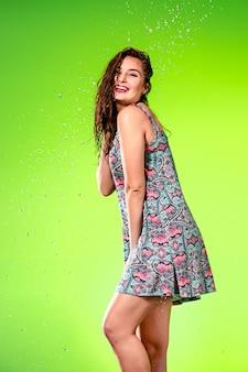 Giovane bella donna sotto la spruzzata di pioggia
