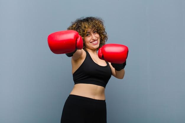 Giovane bella donna sportiva che indossa abiti fitness e guantoni da boxe