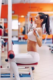 Giovane bella donna sportiva con l'ente perfetto che fa gli allenamenti in una palestra