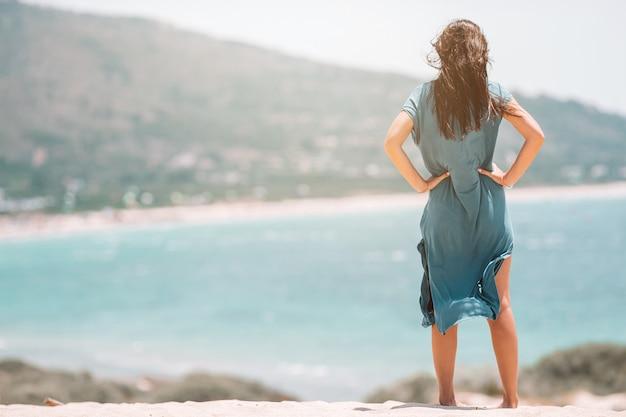 Giovane bella donna sulla spiaggia tropicale bianca.