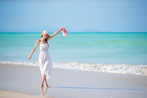 Giovane bella donna sulla spiaggia tropicale della sabbia bianca