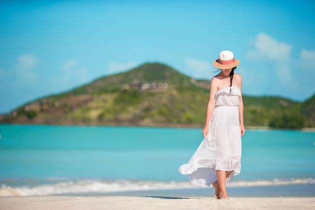 Giovane bella donna sulla spiaggia tropicale