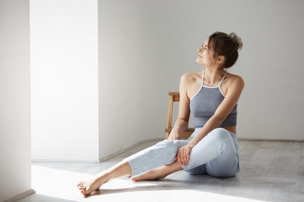 Giovane bella donna tenera che sorride esaminando finestra che si siede sul pavimento sopra la parete bianca.