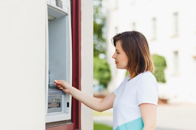 Giovane bella donna utilizzando un bancomat