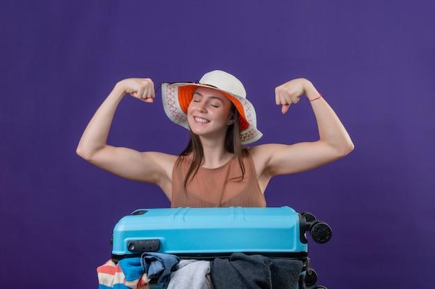 Giovane bella donna viaggiatore in cappello estivo con la valigia piena di vestiti alzando i pugni mostrando bicipiti e forza ottimista e felice sorridente sul muro viola