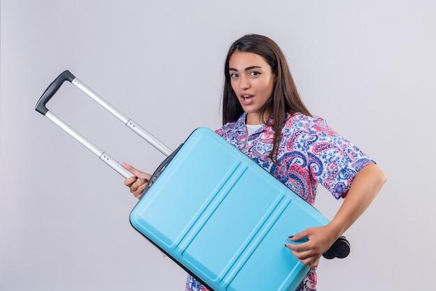 Giovane bella donna viaggiatore tenendo la valigia guardando fiducioso positivo e felice pronto a viaggiare in piedi su sfondo bianco