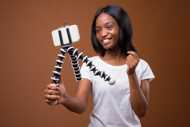 Giovane bella donna zulù africana su sfondo marrone