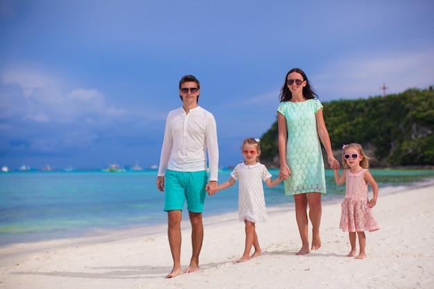 Giovane bella famiglia con due bambini che camminano in vacanza tropicale